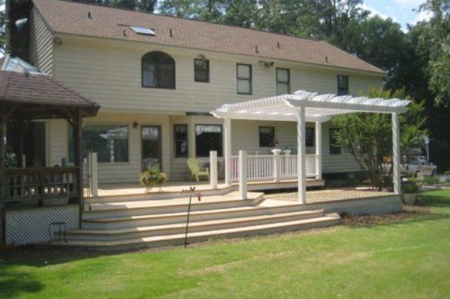 white pergola installation with railing Wilson, NC